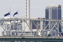 Flags fly at half mast on the Auckland Harbour Bridge in memory of those who died it the Christchurch earthquake. Photo / Paul Estcourt