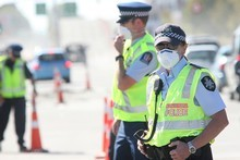 An Australian Federal Officer guards a road cordon on Sunday. Photo / Greg Bowker