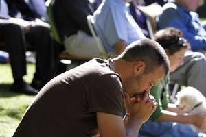 A young man prays during a church service held on the lawn of the Colombo Street Library in Christchurch. Photo / Getty Images