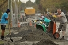 Students work in the suburb of Shirley to clear away silt caused as a result of liquefaction. Photo / Getty Images