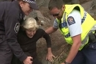 Redcliffs resident Jan Currie is helped to safety by rescue workers.