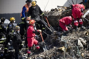 China USAR members assist New Zealand USAR members as they slowly search through the rubble of the CTV Building. Photo / Dean Purcell