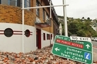 fallen street sign rests in rubble in Lyttelton. Photo / Getty Images
