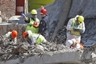 Police officers slowly search through the rubble of the CTV Building. Photo / Dean Purcell