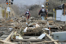 Volunteer firefighters walk along train tracks covered with tsunami-drifted debris in Rikuzentakada, Iwate Prefecture. Photo / AP