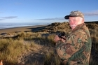 Mike Jarvis watches from the sandhills for any sign of the tsunami. Photo / Herald on Sunday