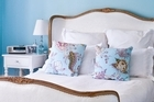 Blue walls and a chandelier give the master bedroom a romantic feel. Photo / Your Home & Garden