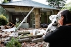 Julie Bos and her dog Murphy at their Heathcote Valley home which was damaged beyond repair in the 6.3-magnitude quake. Photo / Brett Phibbs