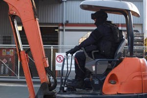 Police use a digger to smash into the Red Devils HQ in Nelson. Photo / Supplied