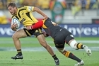 Jack Lam of the Hurricanes is tackled by Isaac Ross of the Chiefs. Photo / Getty Images