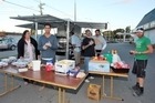 A team of volunteers serve food from a portable BBQ for the people in Aranui, Christchurch. Photo / NZPA