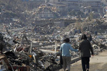 A couple walk along the rubble at a residential area in Onagawa, Miyagi Prefecture, northern Japan after Friday's quake. Photo / AP