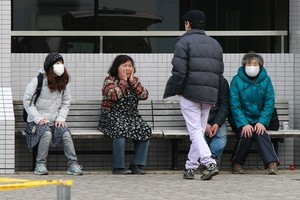 Relatives of tsunami victims wait outside an emergency morgue in Iwaki City. Photo / AP