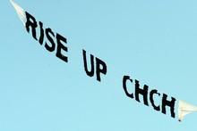 A banner flies over the Earthquake Memorial Service at Hagley Park, Christchurch. Photo / NZPA/Ross Setford