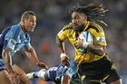 Hurricanes' Ma'a Nonu gets past Luke McAlister of the Blues at Eden Park last night. Photo / Getty Images