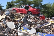 A car on top of a pile of rubble on Bealey Ave. Photo / Geoff Sloan