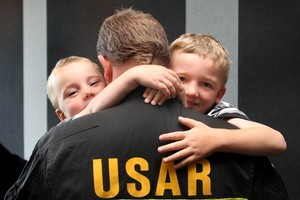 Louis Cairns, 3 (L), and brother Cooper, 5, welcome their father Campbell home at Auckland Airport. Photo / Natalie Slade