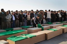Men gather at a mass funeral for people Libyan authorities claim were killed in coalition bombings. Rebels have accused Gaddafi's troops of taking bodies from the morgue. Photo / AP