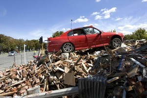 A car sits atop a demolished building in the Christchurch CBD. Police say around 2500 cars have now been recovered from the devastated city centre. Photo / The Listener