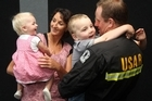 Campbell Cairns cuddles his kids Lewis, left, and Cooper as wife Ronnie and daughter Jess look on. The  USAR team has arrived back at Auckland International Airport after a week in the earthquake and tsunami ravaged Japan. Photo / NZPA