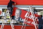 Contractors remove a billboard yesterday from outside Darren Hughes' office in Levin. Photo / Mark Mitchell