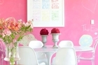 Having painted the entire house white, the Emiralis then introduced colour, such as hot pink in the dining area. Photo / Your Home & Garden