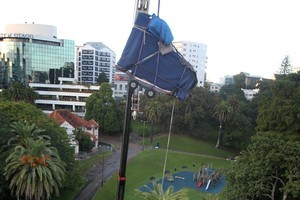 Wrapped in a blue tarpaulin, the piano is hoisted skyward by the crane. Photo / NZPA