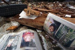 Photo albums lie open in the ruins of Rikuzentakata. many of those in the pictures are still missing. Photo / Bradley Ambrose