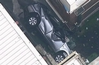 The car was wedged between two buildings after falling up to six floors. Photo / NineMSN