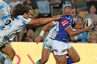 Johnathan Thurston of the Cowboys is tackled by Ryan James of the Titans. Photo / Getty Images
