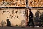 A Libyan man walks past graffiti on a wall reading 'Yes for Free Libya' in Benghazi. Photo / AP