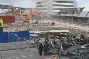 Diggers demolish the row of shops on the east side of Colombo Street in Sydenham. Photo / Geoff Sloan