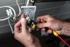 Electrician Bryan Arthur installs a towel rail timer. Photo / Natalie Slade