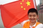 Guide Bobby Peng shows off the Chinese flag and translates stirring slogans. Photo / Phil Taylor