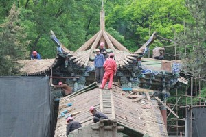 Workers restore the old temple. Photo / Jim Eagles