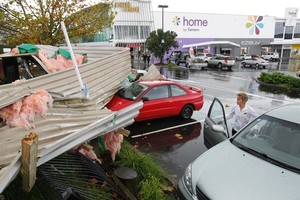 Iron from a roof rests on top of cars parked at the Albany Mega Centre. Photo / Brett Phibbs