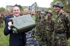 Prime Minister John Key tests the weight of a jerry can while meeting with Limited Service Volunteer trainees at Trentham, after announcing the Government is to spend $55 million on youth jobs. Photo / Mark Mitchell