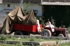 A tractor trolley carries the wreckage of a helicopter that crashed next to Osama bin Laden's Pakistan hideout. Photo / AP