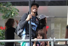 Breakers' guard CJ Bruton takes part in the parade up Queen St with his son. Photo / Paul Harper 
