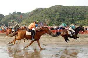 Karekare beach races are a fun day out, hats and all. Photo / Ted Scott