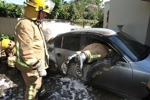A firefighter goes in through the window to retrieve valuables from a car which burst into flames in a driveway after an electrical fault melted its fuel tank. Photo / APN