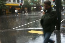 A pedestrian in downtown Auckland moves quickly to avoid heavy rainfall which began falling in the city around midday. Photo / nzherald.co.nz