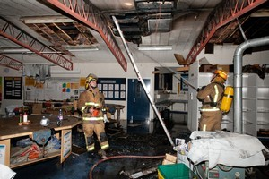 Firefighters inside one of the fire damaged classrooms in the Technology Centre at Fairfield Intermediate School last night. Photo / NZPA/Stephen Barker.