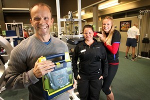 Mark Walley (left) holds the defibrillator trainers Fiona Norton (centre) and Lynley McBride used to save him. Photo / Alan Gibson