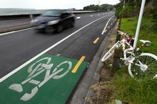 The slippery white line on Tamaki Drive. The 'ghost' bike signifies that cyclist Jane Bishop was killed nearby. Photo / Brett Phibbs