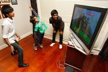 Matthew (left), Elijah (centre) and Mark play games on the family EyeToy. Photo / Steven McNicholl