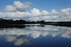 Fluffy clouds and sapphire sky are mirrored in Mangawhai's still, clear estuary. Photo / Liz Light