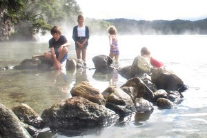Kids enjoying the hot waters at Te Rata Bay. Photo / Alex Robertson