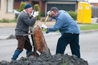 Paul Taylor, left, and Bill Bayfield help clear liquefaction silt. Photo / David Alexander