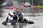Cohl Carrington and Finn Jefferies make their way down a flooded street in Whakatane. Photo / Troy Baker